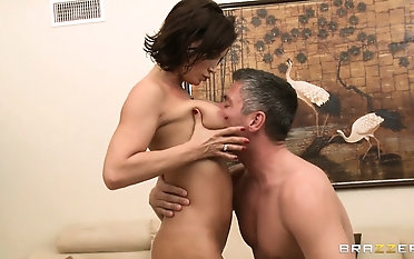Oiled ass of big-breasted brunette is bonked in doggy-style position