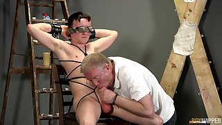 Old supplicant sucks twink's dick during their BDSM uncaring carry on
